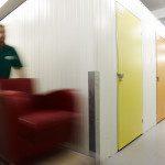 Removal man inside storage unit moving a sofa